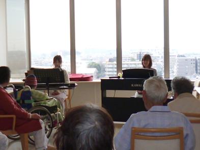 奏者2名が病棟のデイルームで、患者さんを前にピアノを演奏しています。